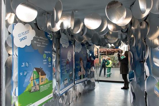 Wnętrze informacyjnego kontenera, na ścianach wiszą liczne plakaty