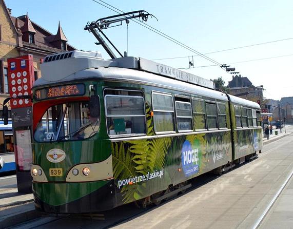 Obklejony w liście oraz zielone grafiki antysmogowy tramwaj przemierzający ulice Katowic